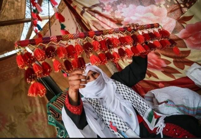 سيدة فلسطينية تغزل الصوف بقرنيْ غزال
